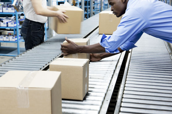 Small corrugated shipping boxes are moving down a conveyor system, with people on either side placing the boxes on it.