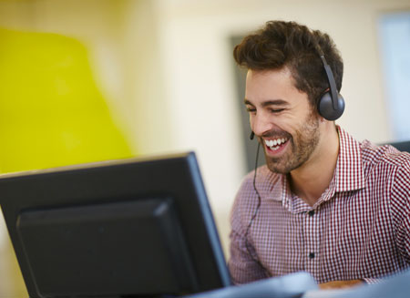 A smiling man wearing a telephone headset uses a computer to create an association shipping program.