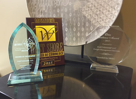 Several awards that PartnerShip has won are sitting on a table.