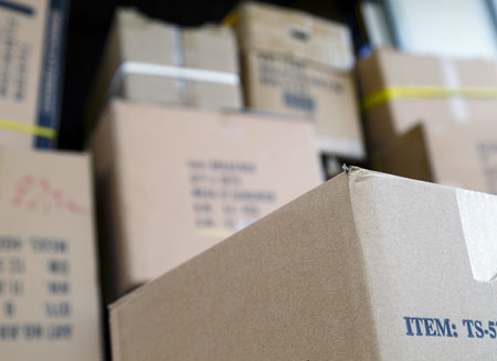 Close up of several cardboard shipping boxes stacking on top of one another.