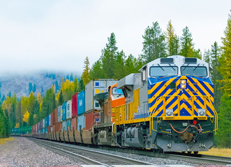 A railroad locomotive pulls a full train of shipping containers loaded on flatcars.