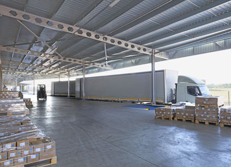 A warehouse is filled with multiple pallets of L T L freight, ready to be shipped.