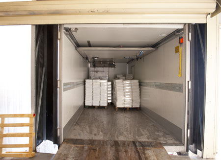 L T L freight is shown in the back of a truck as it sits at a loading dock.