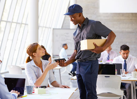 A man wearing a uniform delivers a small package to a woman in an office.