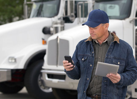 A truck driver wearing a blue jacket and blue cap stands in front of several white trucks, looking at his smart phone.