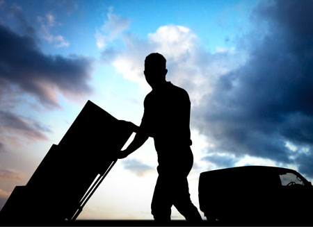 A silhouette of a man delivering several small packages on a dolly.