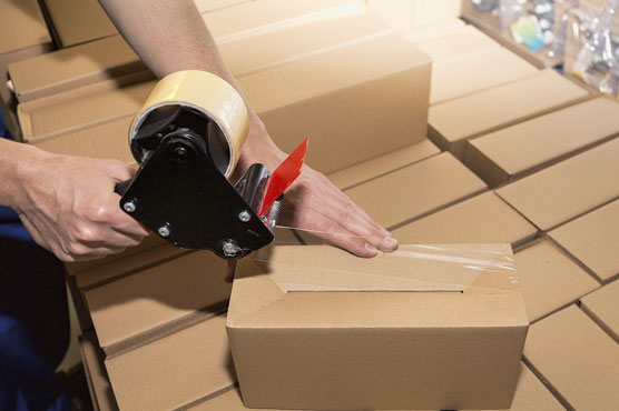 A tape gun is being used to apply clear packing tape to a small cardboard box to seal it for shipping.